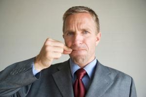businessman_zipping_mouth